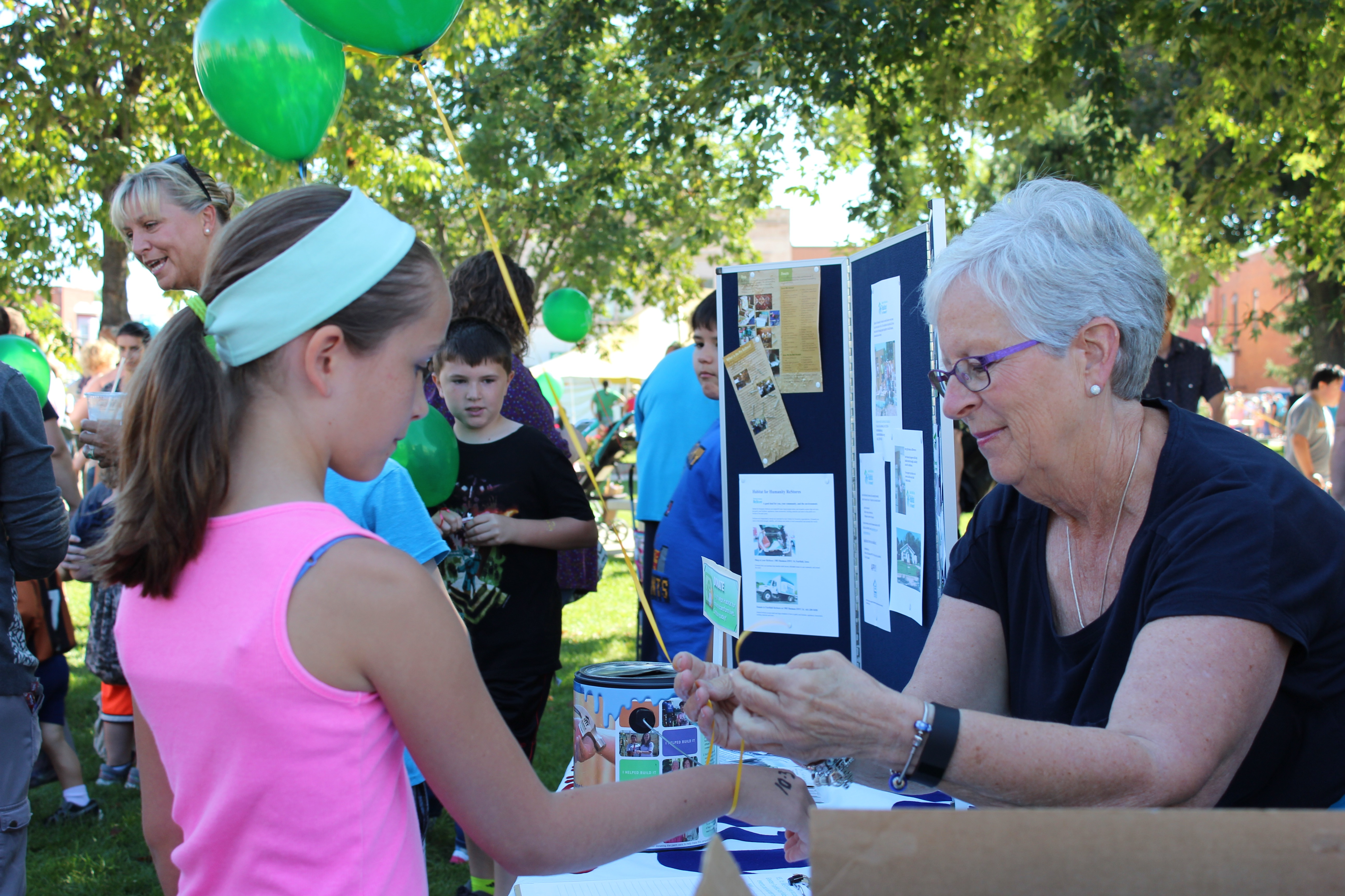 Board member Deb Johnson helps with balloons at the Kiwanis Kids' Day on the square.